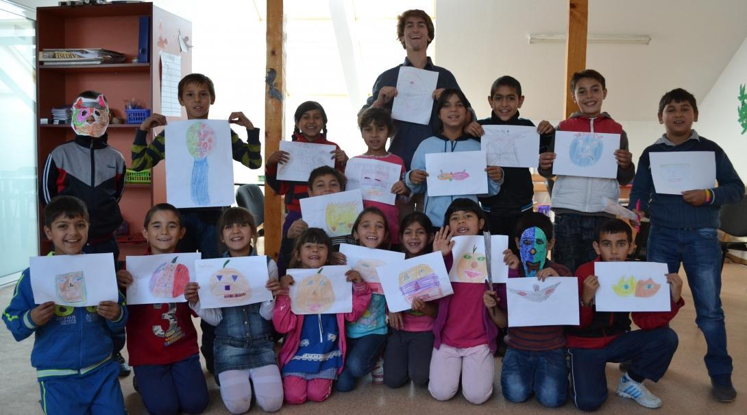Projects Abroad male volunteer with children holding their drawings at a Childcare placement in Romania.